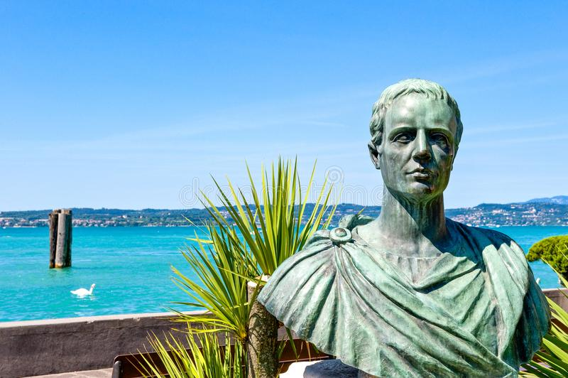 The colorful villages on the Garda Lake. Italy,Garda lake,Sirmione,the bronze bust of Catullo on the shore of the lake royalty free stock image