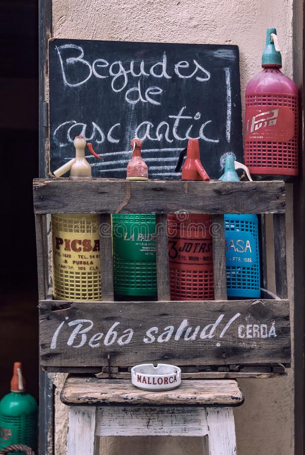 Colorful vintage soda bottles on display in a rustic wooden crate at a wine store with a sign in Catalan that reads Old town. Palma de Mallorca, Spain - October royalty free stock photography