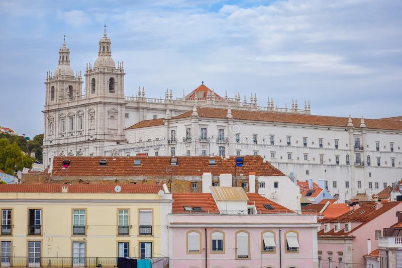 Colorful walls of the buildings of Lisbon, with orange roofs and the Church of Sao Vicente of Fora in the background. Sunny day stock images