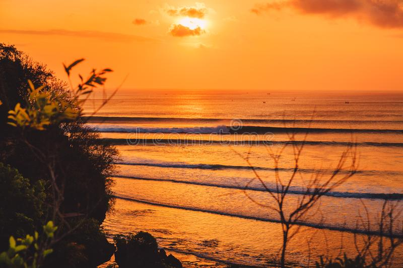 Colorful warm sunset or sunrise with ocean and perfect waves fo surfing stock photography