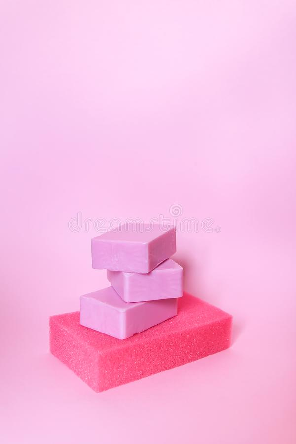Washcloths and bars of soap on a soft pink background. Accessories for body care and hygiene. Colorful washcloths and bars of soap on a soft pink background royalty free stock photos
