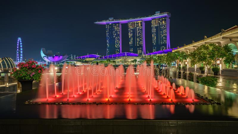 Singapore - october 14, 2018: water fountains in front of marina bay sands and singapore flyer at night. Colorful water fountains in front of marina bay sands royalty free stock images