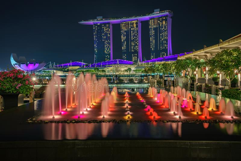 Singapore - october 14, 2018: water fountains in front of marina bay sands and singapore flyer at night. Colorful water fountains in front of marina bay sands royalty free stock photos