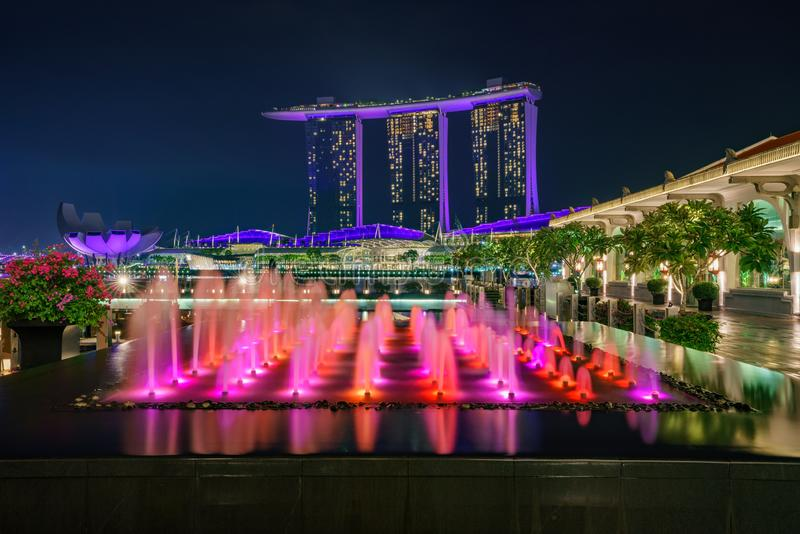 Singapore - october 14, 2018: water fountains in front of marina bay sands and singapore flyer at night. Colorful water fountains in front of marina bay sands royalty free stock image