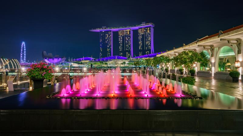 Singapore - october 14, 2018: water fountains in front of marina bay sands and singapore flyer at night. Colorful water fountains in front of marina bay sands stock photography