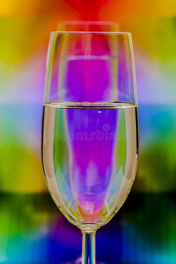 Colorful water. Glass of water in front of a special background creating a unique image with reflected colorful lines