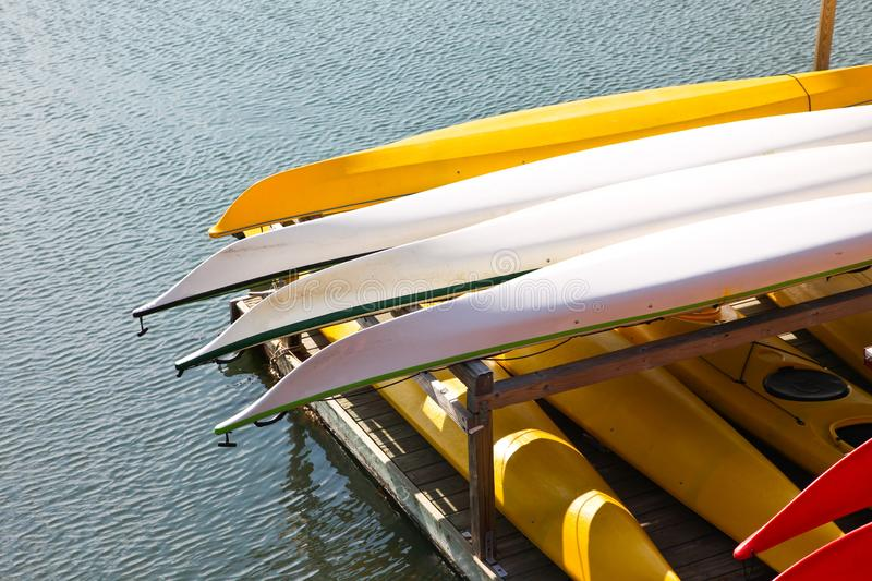 Colorful water kayaks on stand near ocean water royalty free stock photos