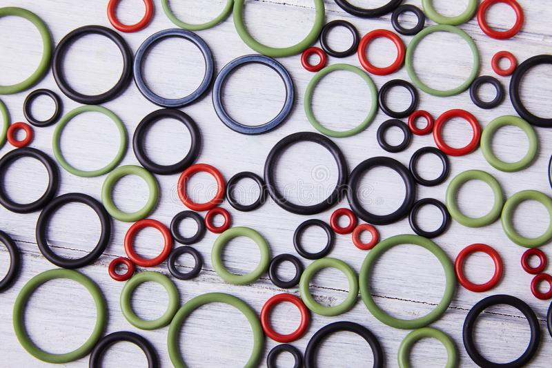Colorful water level rubber gaskets scattered on the woodenbackground. Top viev. Rubber sealing gaskets stock photo
