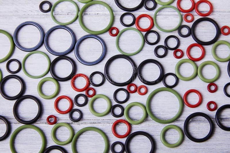 Colorful water level rubber gaskets scattered on the woodenbackground. Top viev. Rubber sealing gaskets stock photography