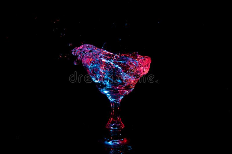 Colorful water overflowing over the side of coctail glass royalty free stock image