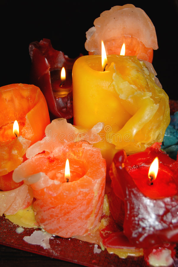 Colorful wax candles. Several colorful burning candles with melted wax in a decorative display stock photos