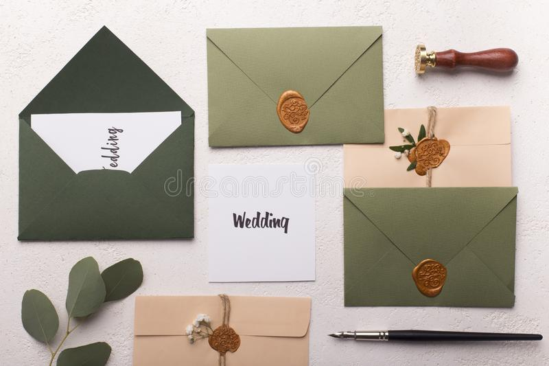 Colorful wedding envelopes with creative invitation text. Composition of colorful wedding envelopes with creative invitation text on white background royalty free stock photography
