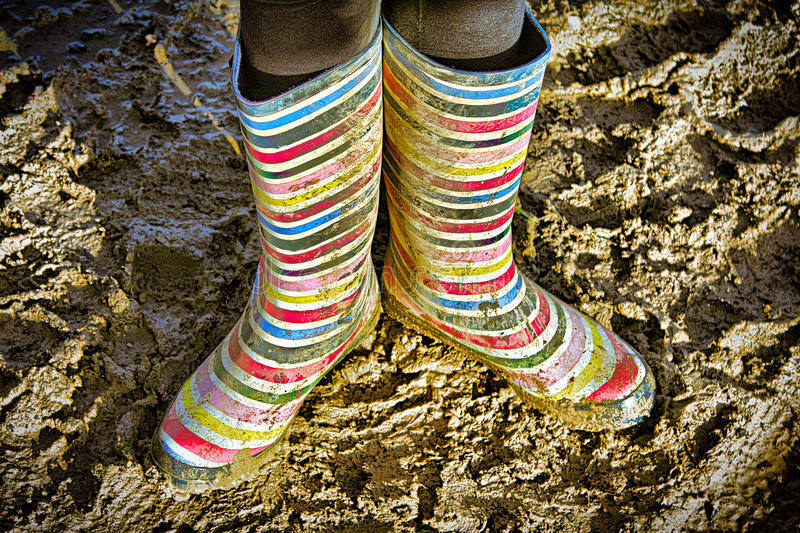 Colorful wellie/gum/rain boots in the mud stock images