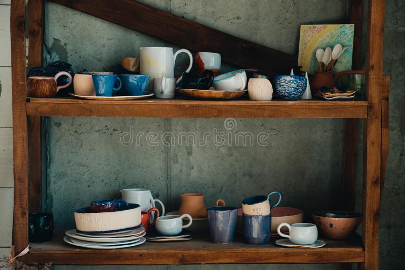 Colorful, white and blue ceramic cups and dishes on shelves of pottery store royalty free stock photography