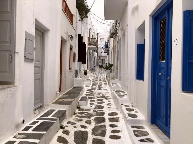 Colorful white streets with blue doors and windows on the island of Mykonos. Greece. Narrow old white streets. Cropped shot, concept of travel and history stock photography