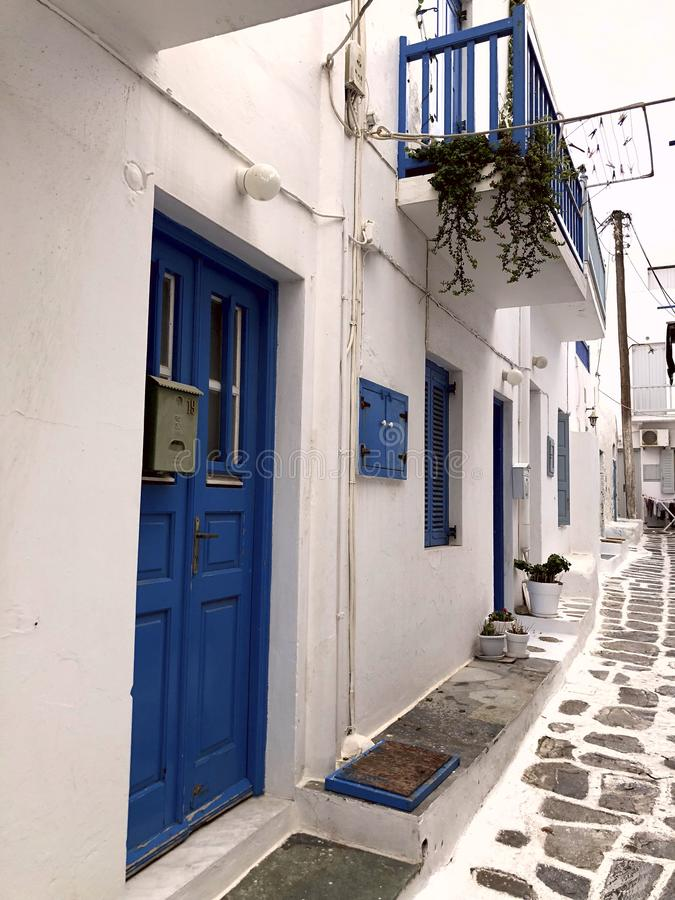 Colorful white streets with blue doors and windows on the island of Mykonos. Greece. Narrow old white streets. Cropped shot, concept of travel and history stock images
