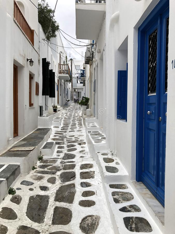 Colorful white streets with blue doors and windows on the island of Mykonos. Greece. Narrow old white streets. Cropped shot, concept of travel and history stock photos