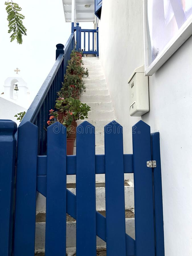 Colorful white streets with blue doors and windows on the island of Mykonos. Colorful white house facade with blue doors and staircase on Mykonos island. Greece stock image