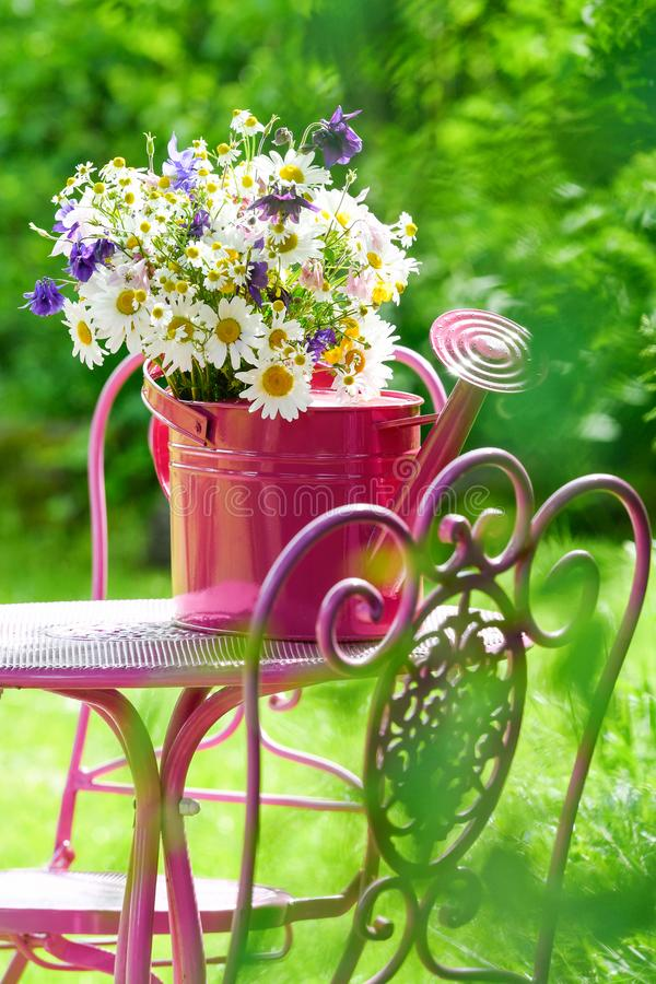 Colorful wild flower bouquet in a pink watering can stock photos