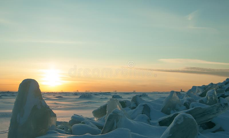 Colorful winter landscape with crystal cracked ice, deserted surface of frozen sea covered by snow and sunset sky. royalty free stock photos