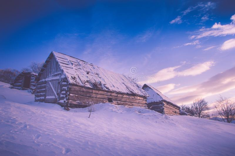 Colorful winter sunrise in the mountains. Fantastic morning glowing by sunlight. View of the snowy forest and old wooden hut cabin stock photos