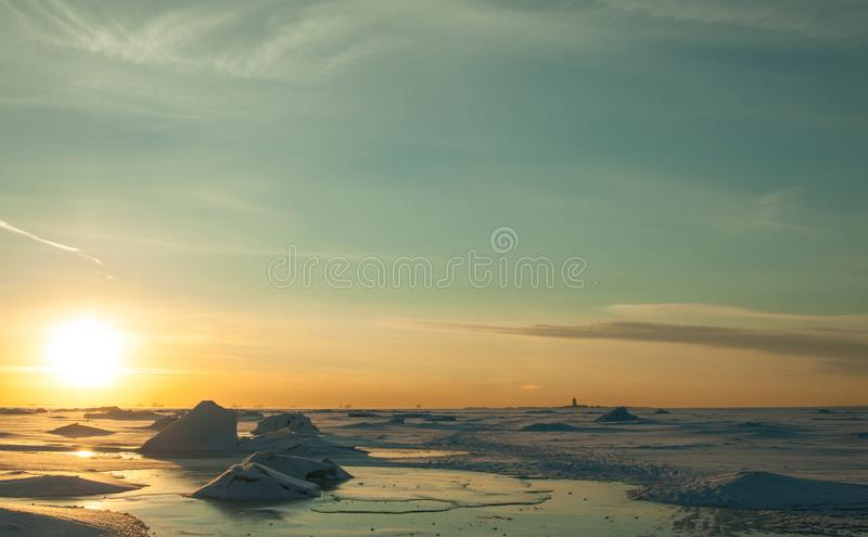 Colorful winter sunset over cracked ice. Deserted surface of frozen sea covered by snow and blue sky with cirrus clouds. royalty free stock photography