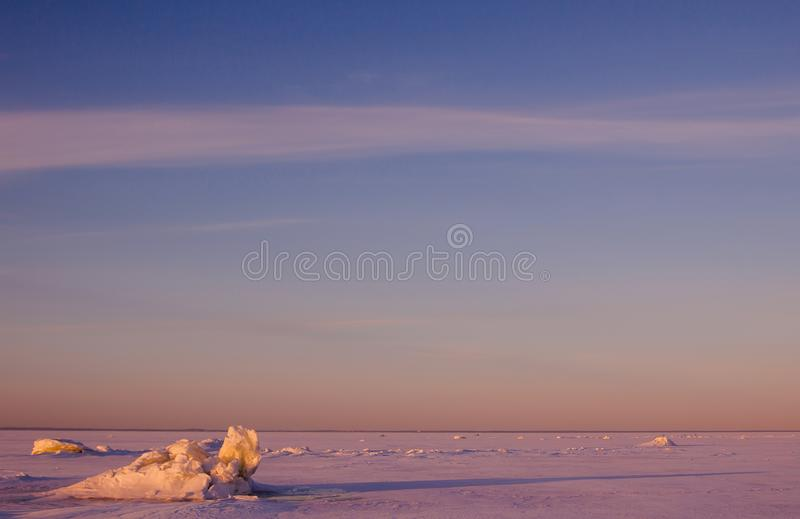 Colorful winter sunset over the cracked pink ice with long shadows. stock image