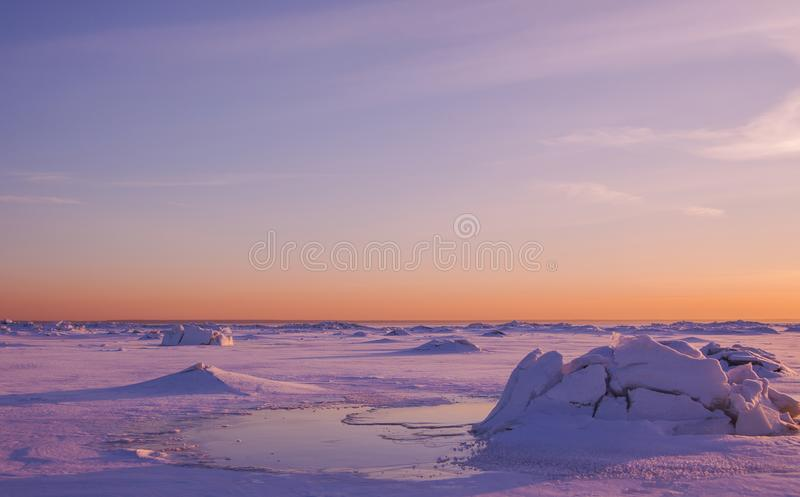 Colorful winter sunset over the deserted surface with cracked pink ice which looks like snow volcano. royalty free stock photo