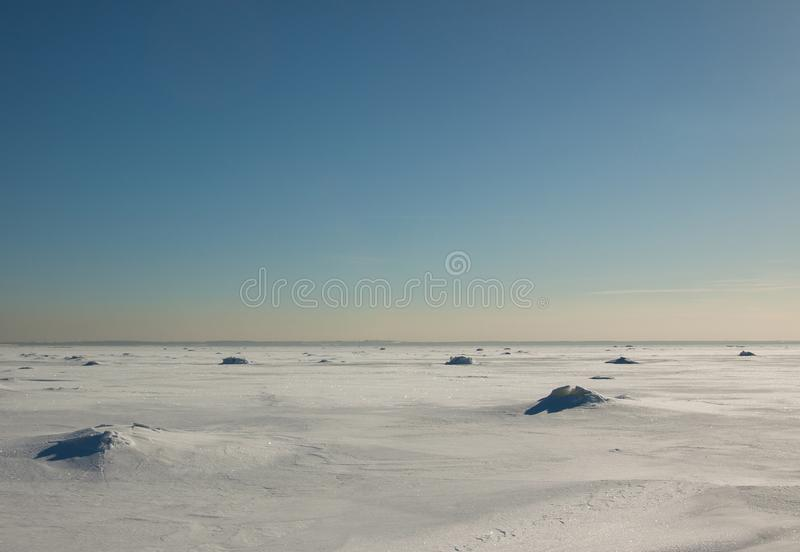 Colorful winter sunset over the deserted surface full of the cracked blue ice. stock image