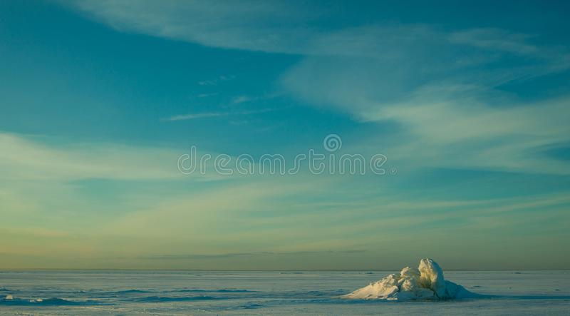 Colorful winter sunset over the deserted surface with lonely cracked blue ice which looks like snow volcano. royalty free stock image