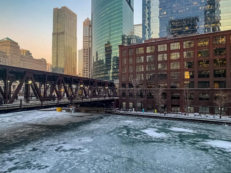 Colorful winter sunset over a frozen Chicago River stock images