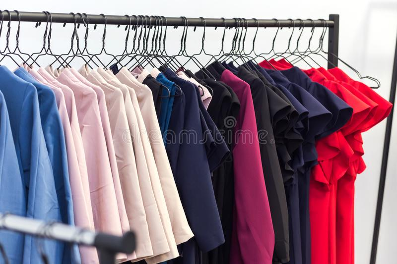Colorful women`s dresses and other clothes on hangers in a retai royalty free stock photos