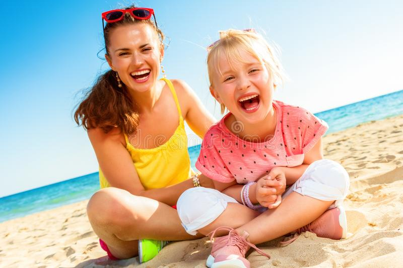 Cheerful modern mother and child sitting on beach royalty free stock image
