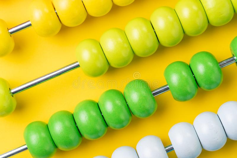 Colorful wooden abacus beads on yellow background, business financial or accounting cost and expense calculation concept, or use. In education school arithmetic stock image