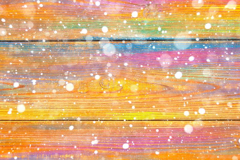 Colorful wooden background and falling snowflakes. Winter background. Christmas spirit royalty free stock photos