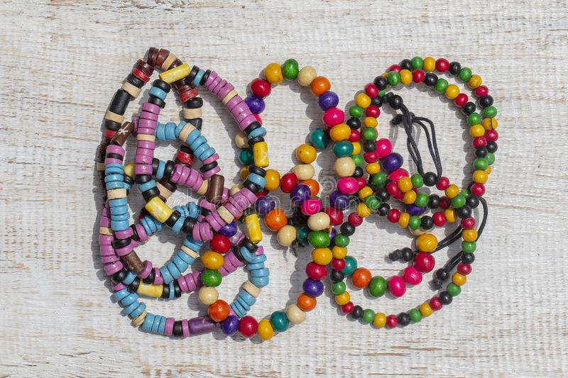 Colorful wooden beads bracelet on white wooden background, close up stock images