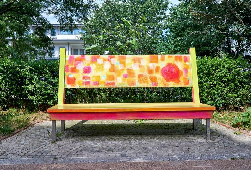 Colorful wooden bench with rose in street art design on the Baltic Sea. Street bank in Binz on the island of Rügen. Colorful wooden bench with rose in street stock images