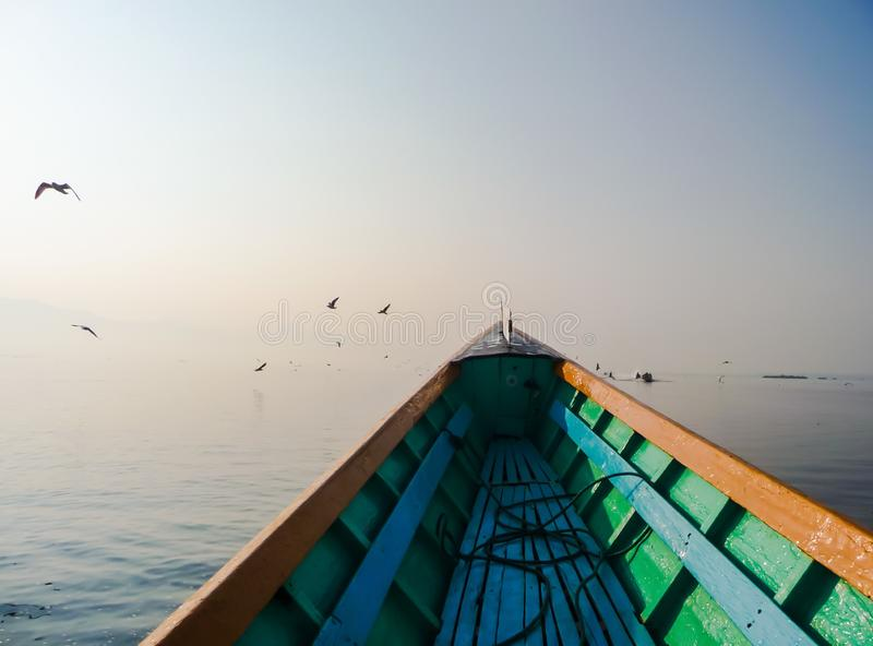 Colorful wooden boat on tranquil water with in front small birds stock photos