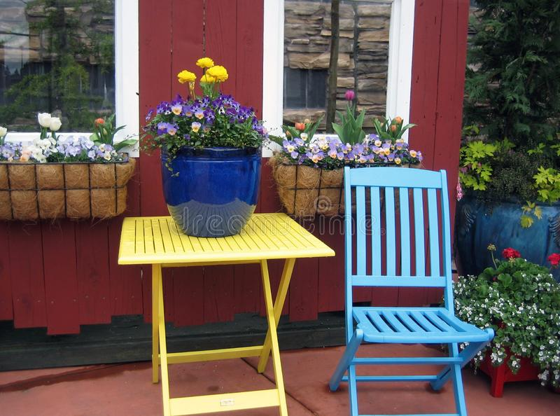 Colorful wooden chair and table with flowers and window boxes royalty free stock photos