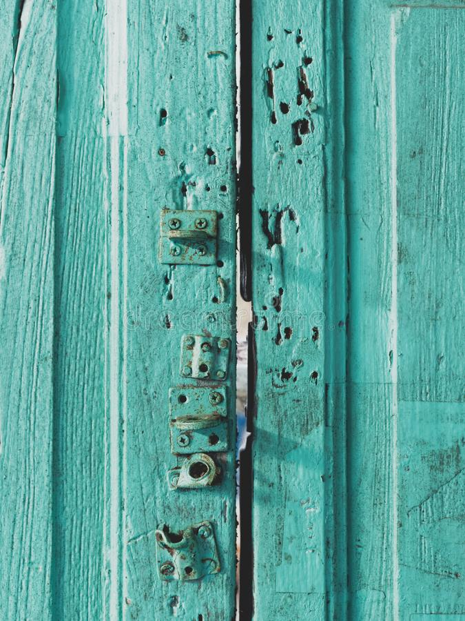 Colorful wooden door surface with lock painted with green, blue, or aquamarine color in vintage and retro style stock photography