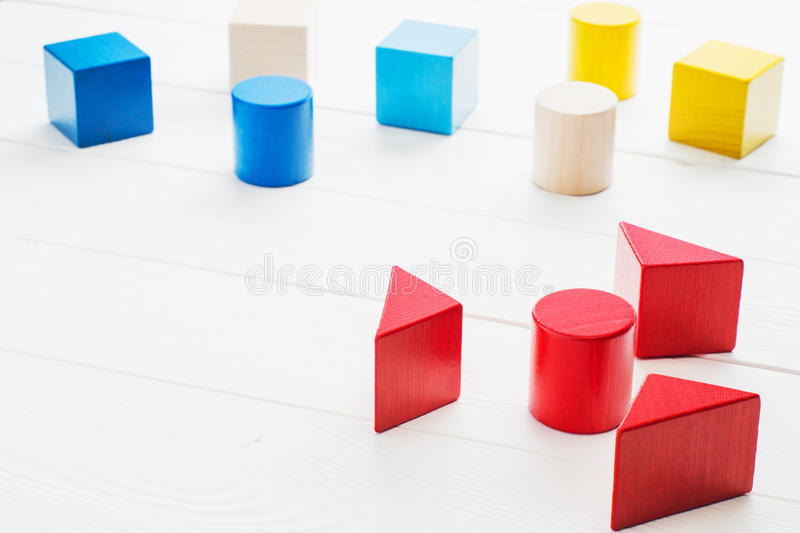 Colorful wooden geometric building blocks on white wooden background. stock photo