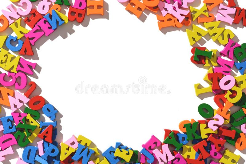 Colorful wooden letters laid out around on a white table. the layout of the isolate. royalty free stock image