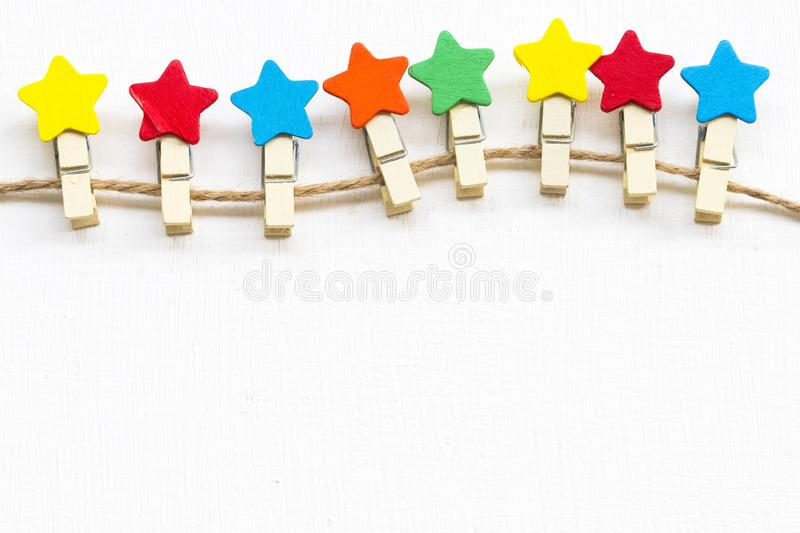 Colorful wooden star clips arrangement flat lay postcard style. On background wooden white royalty free stock photo