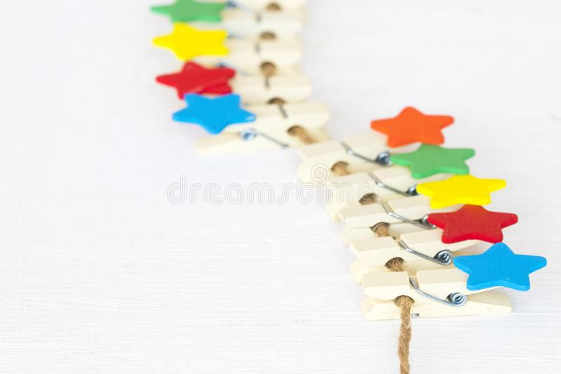 Colorful wooden star clips arrangement flat lay postcard style. On background white royalty free stock image