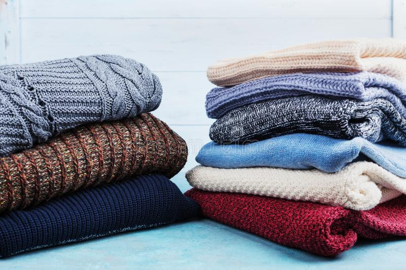 Colorful wool sweaters and knitted winter clothes on blue wooden background. stock images