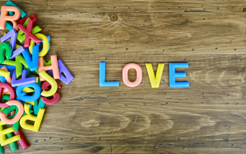 The colorful word `LOVE` next to a pile of other letters royalty free stock images