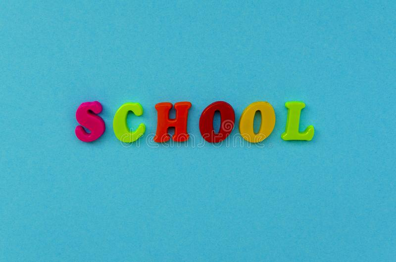 Colorful word `school` of magnetic letters on blue paper background. Colorful word `shcool` of magnetic letters on blue paper background royalty free stock image