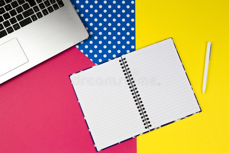 Colorful workplace. Laptop computer, open paper notebook and white pen on colorful background royalty free stock photography
