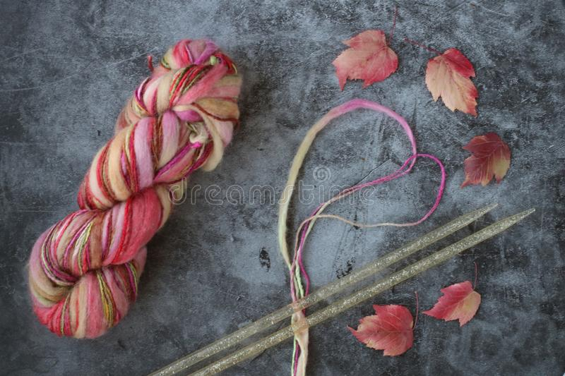 Colorful yarn ball looking like rainbow, two thick needles, segment of yarn like heart and red leaves on grey background stock images