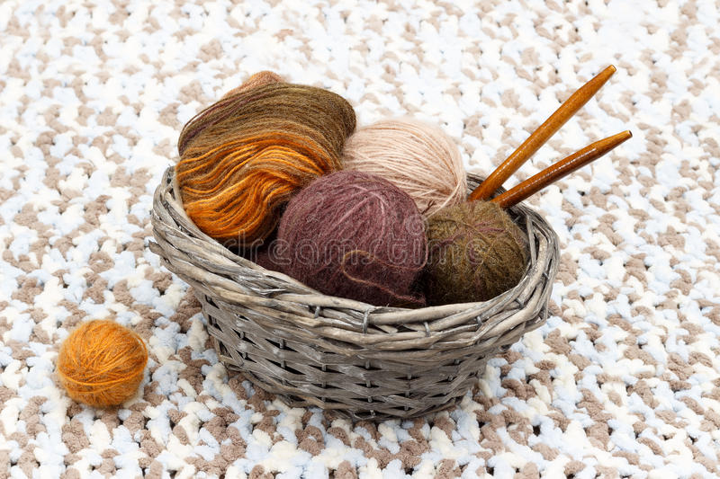 Colorful yarn in balls and coil and wooden needles lies in braided basket stock photography